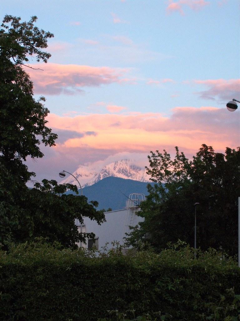 Sunset pink clouds atop mountains